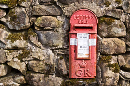 inlaid: Welsh letterbox inlaid into a stone wall. Stock Photo