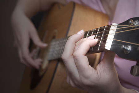 young woman playing an acoustic guitar. Stock Photo