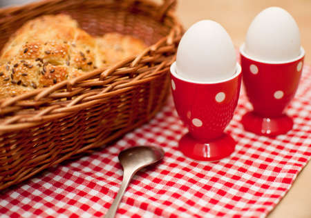 hard boiled: Hard Boiled Eggs and Rolls in Basket on Table Stock Photo