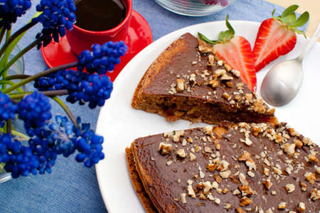 Walnut Cake With Strawberries and Cup of Coffee on Table photo
