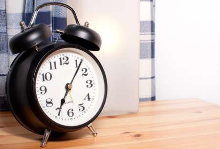 despertador: Despertador y l�mpara de lectura en mesa de cabecera Foto de archivo