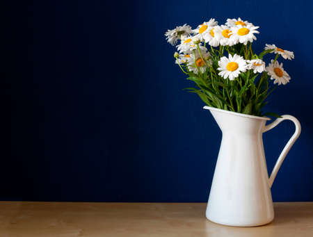Fresh Oxeye Daisies on table in white Pitcher in interior  photo