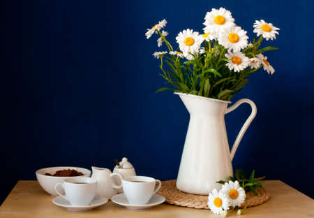 Coffee Mugs and Fresh Oxeye Daisies on wooden table in interior  photo