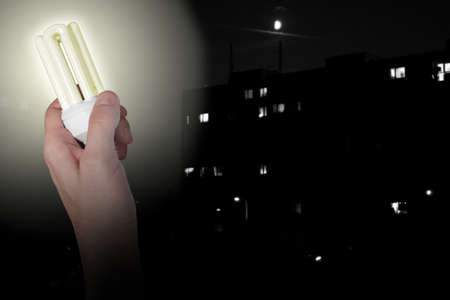 Glowing Energy Saving Bulb in Hand on Dark City Background Stock Photo - 9904119
