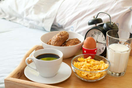 Breakfast in Bed - Rolls, Coffee, Boiled Egg, Milk, Corn Flakes and Alarm Clock photo