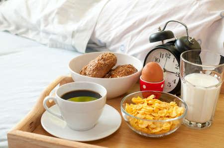 dejeuner: Petit d�jeuner au lit - Rolls, caf�, bouillie ?ufs, lait, Corn Flakes et r�veil Banque d'images