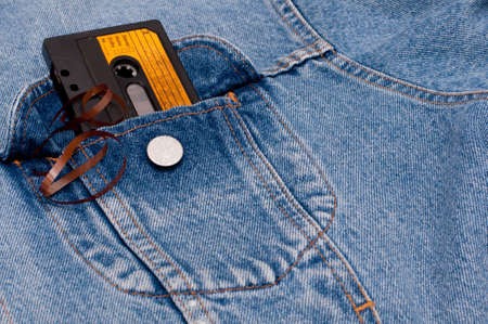 jeans pocket: Retro Music - Old Audio Cassette Tape in Pocket of Blue Jeans Jacket Stock Photo