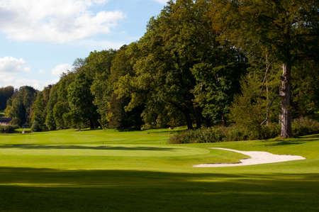 golfcourse: Golf Course In Forest - Green With Flag and Bunker Stock Photo