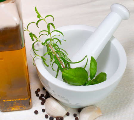 marinate: Marinade for barbecue in Mortar - Rosemary, basil, garlic, pepper and olive oil on table Stock Photo