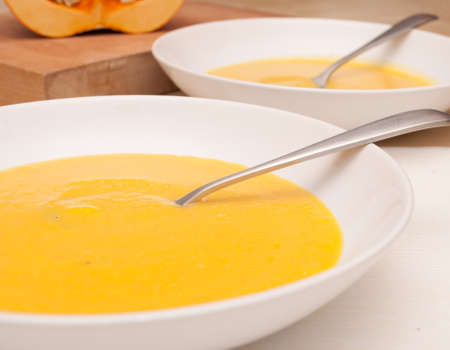 butternut squash: Plates of Butternut Squash Soup on Table
