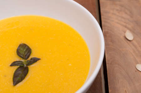 Bowl of Butternut Squash Soup on Old Wooden Table photo