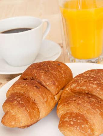 Petit-déjeuner - croissants, café et jus d'orange sur le tableau en bois
