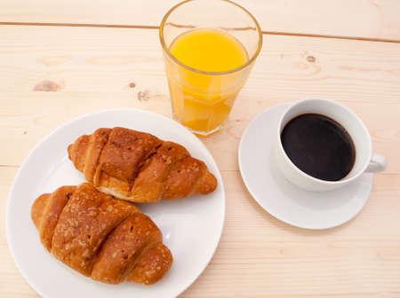 Desayuno - croissants, café y jugo de naranja en la tabla de madera Foto de archivo