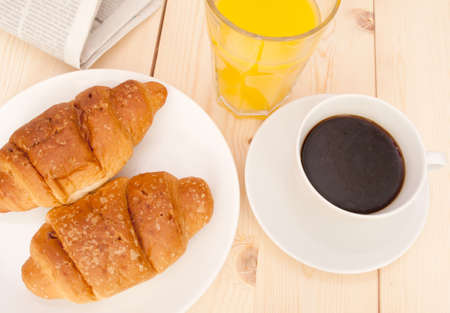 Breakfast - Croissants, Coffee, Orange Juice and Newspapers on Wooden Table Stock Photo - 10765639