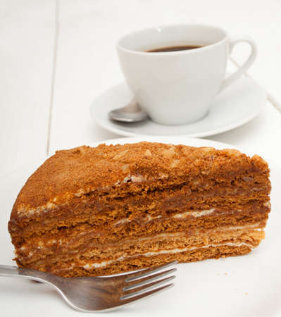 walnut cake: Traditional Honey Cake on Plate and White Cup of Coffee on Table