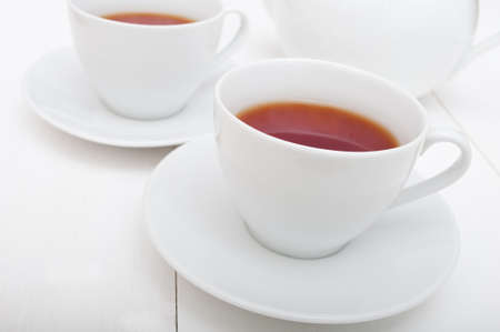 White Cups of Tea and Teapot on White Table Stock Photo - 11132950