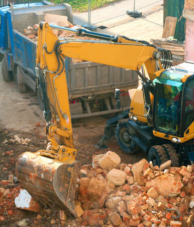demolition: Digger and Truckload of Rubble in House Under Demolition Editorial