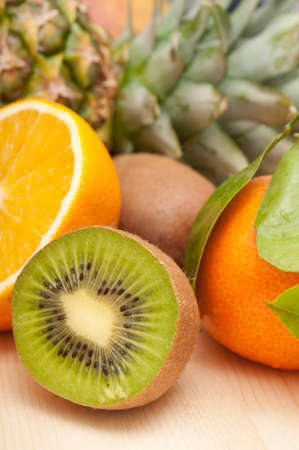 Tropical Fruits - Pineapple, Oranges, Tangerine and Kiwi on Wooden Table Stock Photo - 11320870