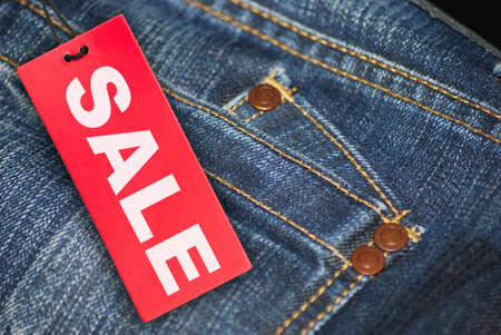 clearance sale: Red Sale Sign With Jeans in Background