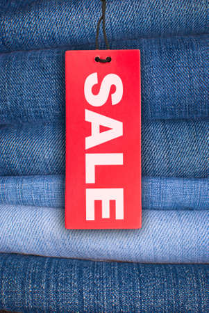 Red Sale Sign With Stack of Blue Jeans in Background photo