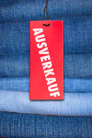 Red German Sale Sign With Stack of Blue Jeans in Background Stock Photo - 11799681