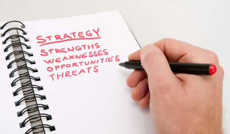SWOT Analysis - Close up of Hand With Red Marker and Open Notebook
