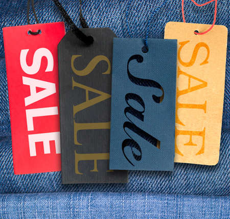 etiquetas de ropa: Etiquetas con signo venta con la pila de jeans azul en el fondo