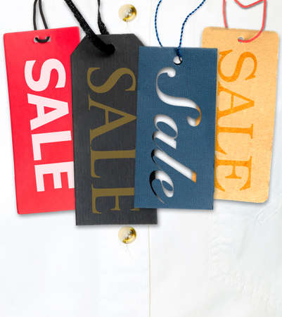 Tags With Sale Sign With Stack of White Shirt in Background photo