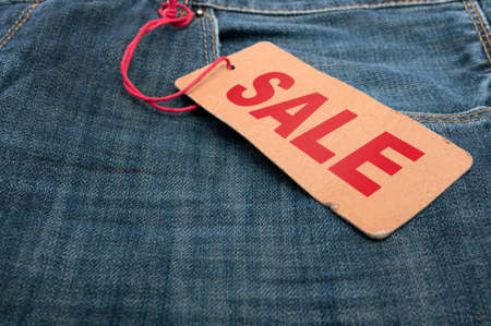 Closeup of Blue Jeans With Brown Sale Tag photo