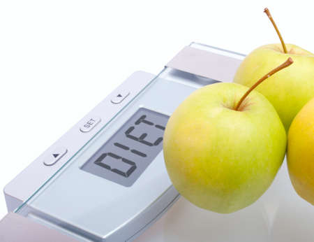 Diet - Green Apples on Bathroom Scales With Diet Sign on Display on White Background Stock Photo - 12597696