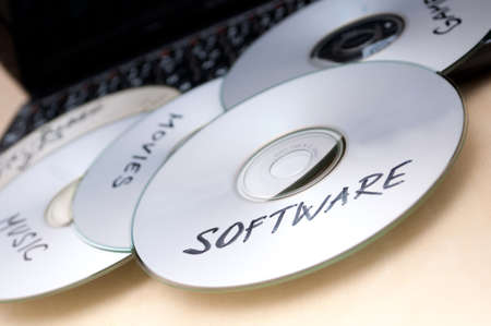 Piracy Concept - Burnt CDs With Illegal Software on Keyboard of Notebook