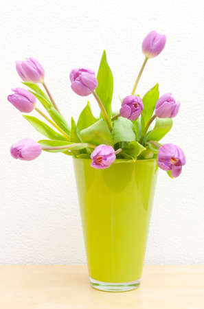 tulips in vase: Pink Tulips Bouquet in Green Glass Vase on Wooden Table Stock Photo