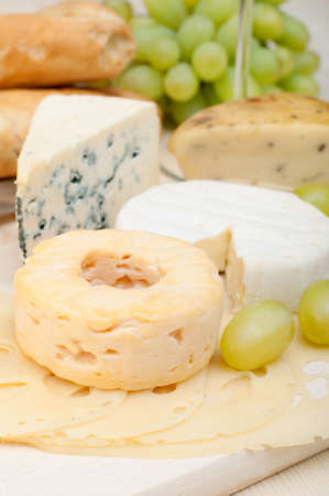 baguet: Various Types of Cheese and Grapes on Wooden Chopping Board