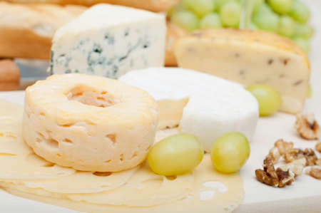 Various Types of Cheese, Grapes and Walnuts on Wooden Chopping Board photo