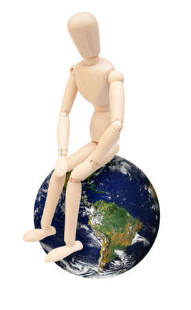 Wooden Puppet Sitting on Earth Globe - Isolated on White  Source image of Earth courtesy of NASA - terms of use  http   visibleearth nasa gov useterms php photo