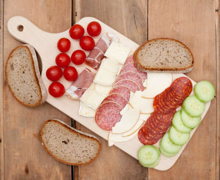 Snack - Salami, Cheese, Vegetables and Bread on Wooden Chopping Board photo