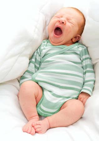 Bostezar bebé recién nacido en la cama