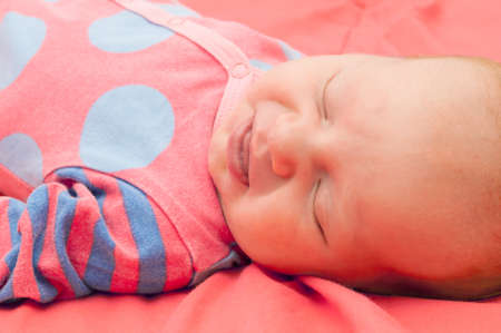 Smiling Newborn Baby Sleeping on Pink Blanket photo