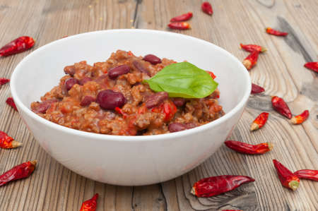 Chilli Con Carne in White Bowl and Red Chili Peppers photo