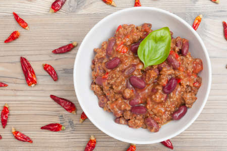 Chilli Con Carne in White Bowl and Chili Peppers photo