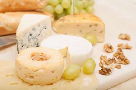 Various Types of Cheese and Grapes on Wooden Chopping Board photo
