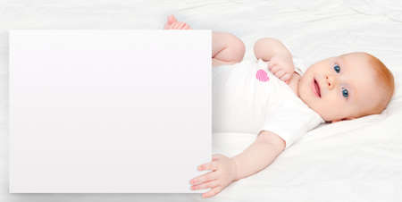 holding a sign: Cute Baby Girl Lying on Back Holding Sign