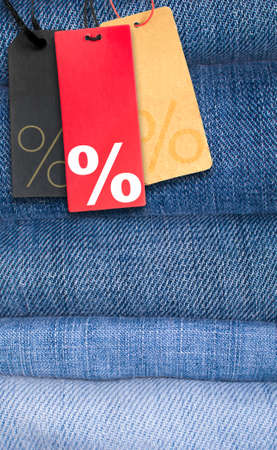 Sale Tags With Percentage Symbol on Stack of Blue Jeans photo