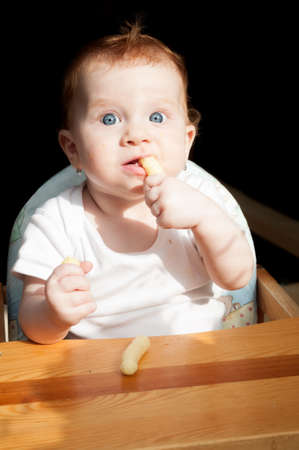nibbles: Cute Toddler Baby Girl Eating Corn Nibbles Stock Photo