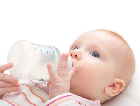 tomando leche: Ni�a de la leche de la botella en el fondo blanco