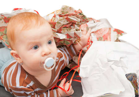 unwrapped: Baby in the heap of christmas wrapping paper Stock Photo