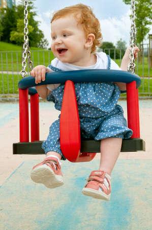 columpio: Feliz niña sentada en un columpio Foto de archivo