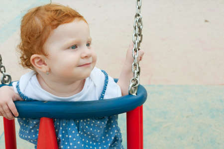 red haired: Happy Baby Girl Sitting in the Swing