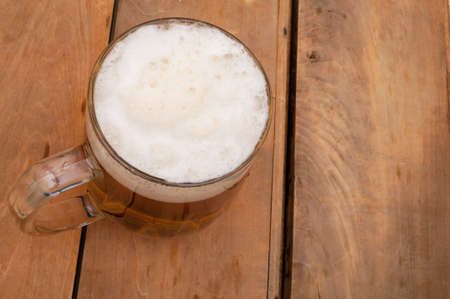 Top View of Glass Full of Beer on Aged Wooden Table  photo