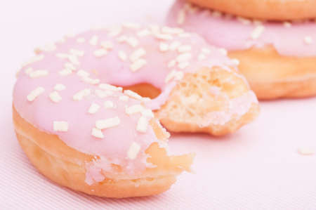 biten: Closeup of Homemade Donuts with Pink Icing - Shallow Depth of Field